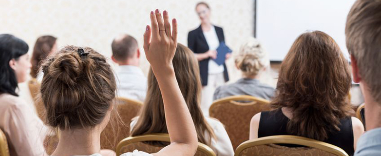 44777147 - photo of listener raising hand to ask question during seminar